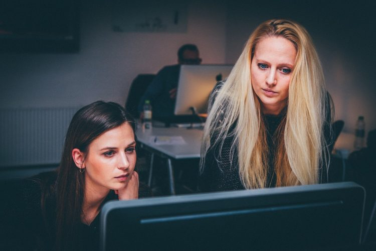 A woman mentors another woman while looking at a computer