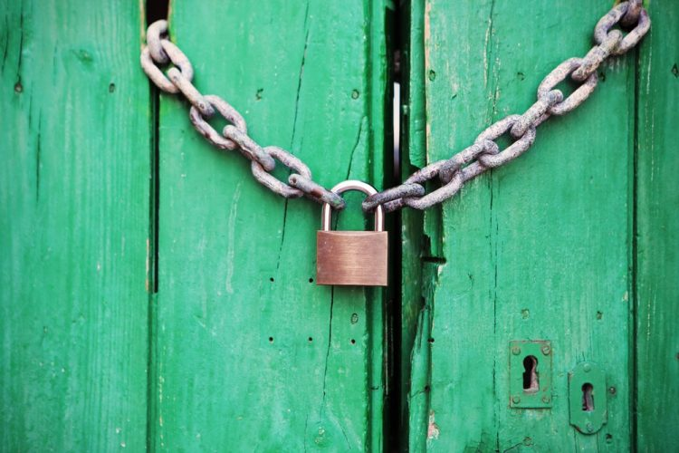 Padlock on a green door