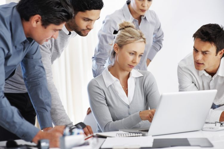 Team of business professional looking at laptop