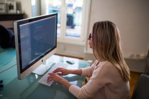 Woman coding on iMac computer