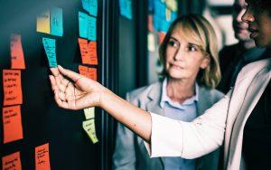 Women holding sticky notes at blackboard